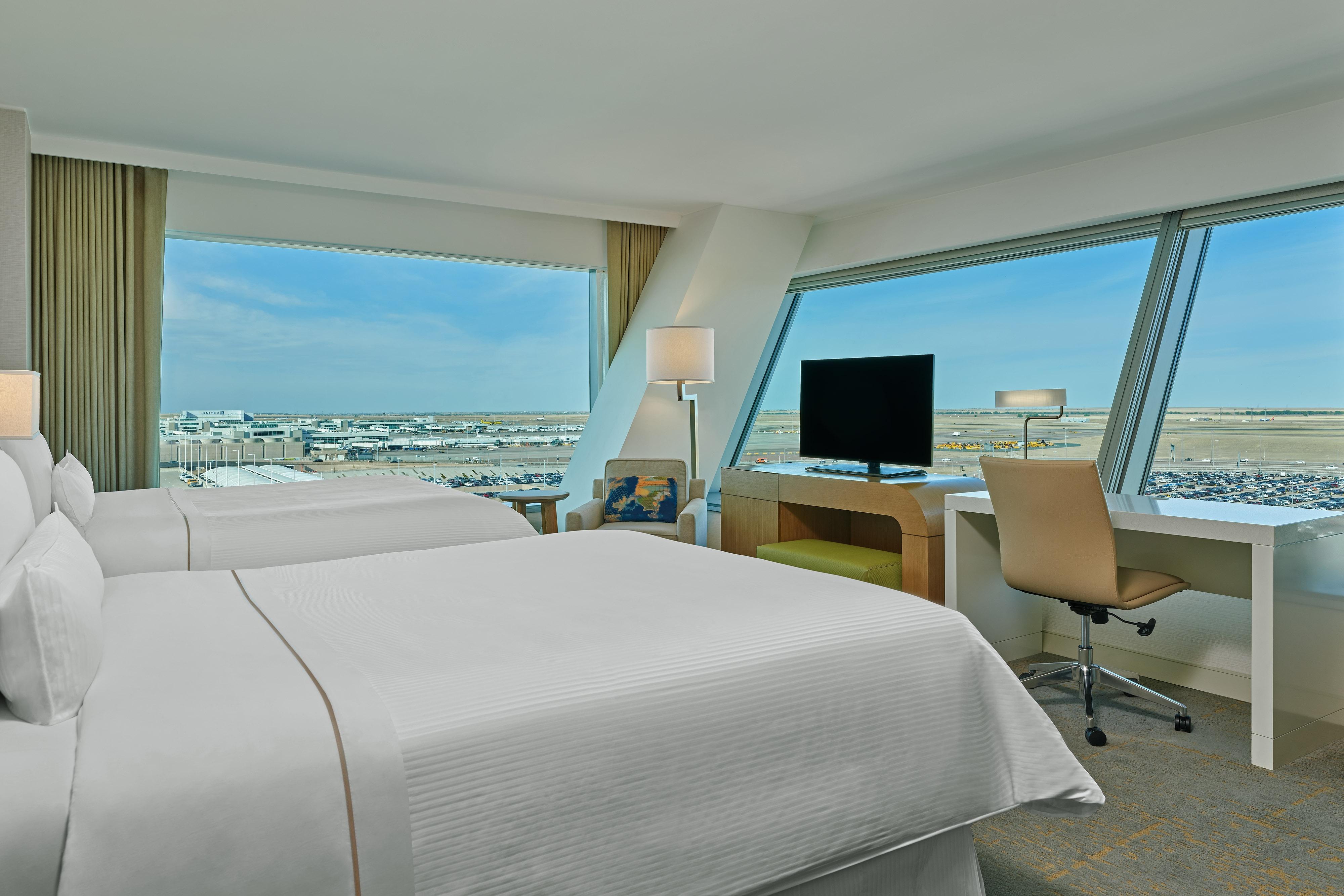 Habitación con dos camas tamaño Queen y vista a la pista de aterrizaje