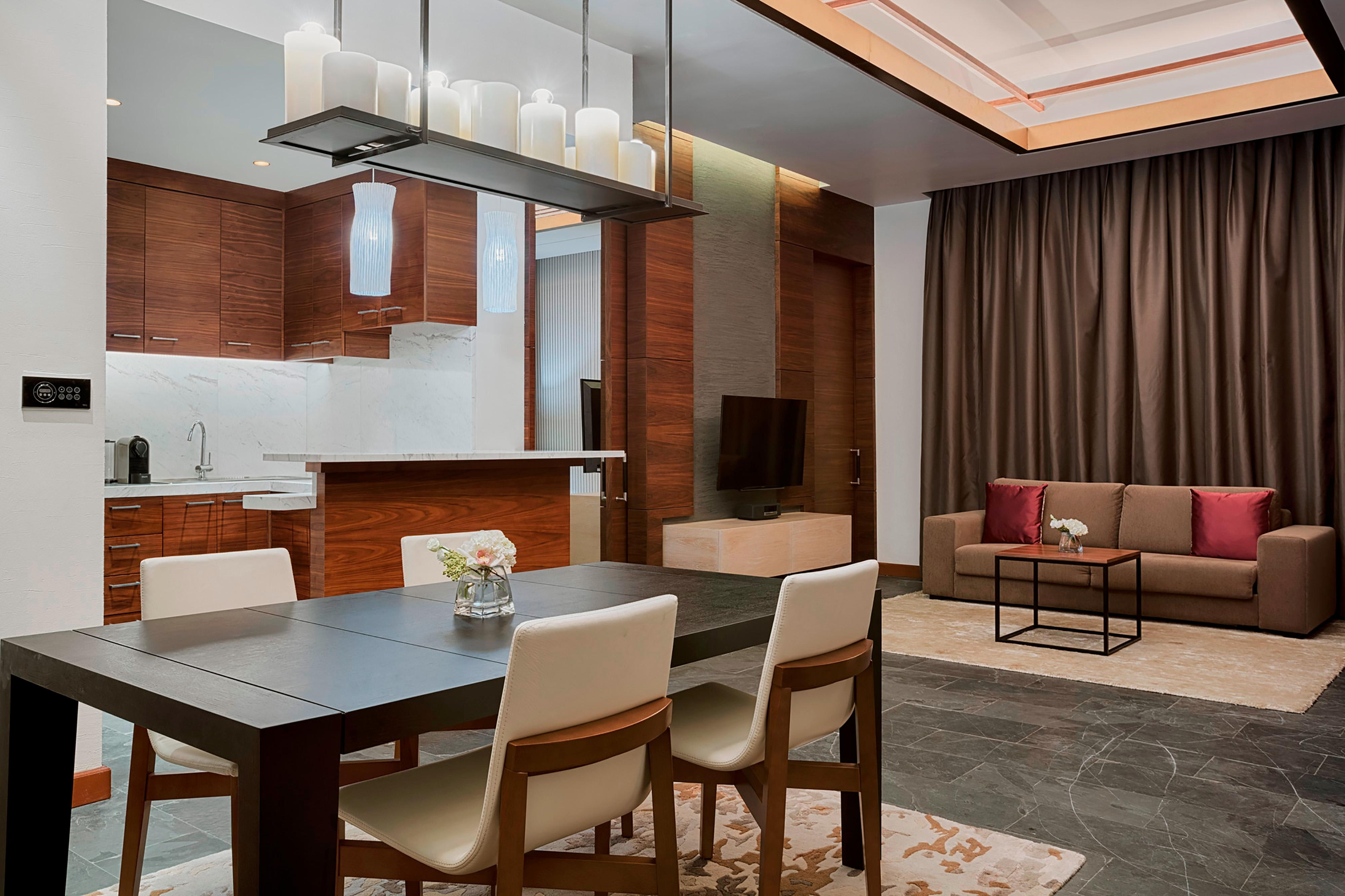 A lavish living area features a large sofa, 55'' LED Flat screen TV and a dining table to seat six coupled with a functional kitchenette for guests convenience.