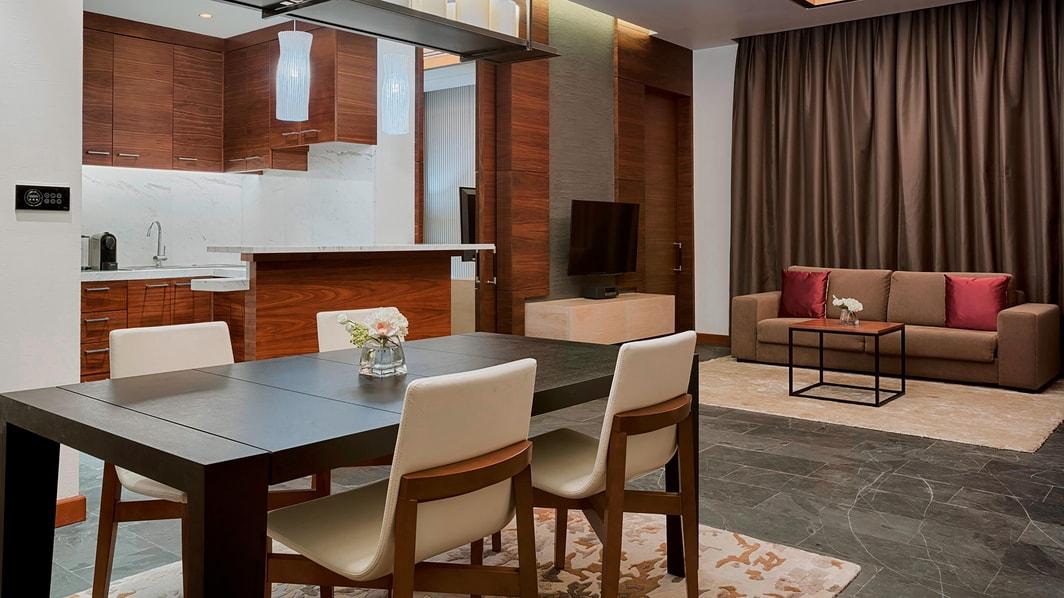 La lujosa sala de estar cuenta con un gran sofá, un televisor de pantalla plana de 55 pulgadas y una mesa de comedor para seis personas con una cocina pequeña para la comodidad de los huéspedes.