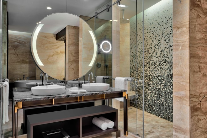 The Bridal Suite bathroom houses a sleek marble floor and vanity sinks, a soaking tub and separate rainforest shower, White Tea by Westin™ bath amenities, and a plush Heavenly bathrobe.