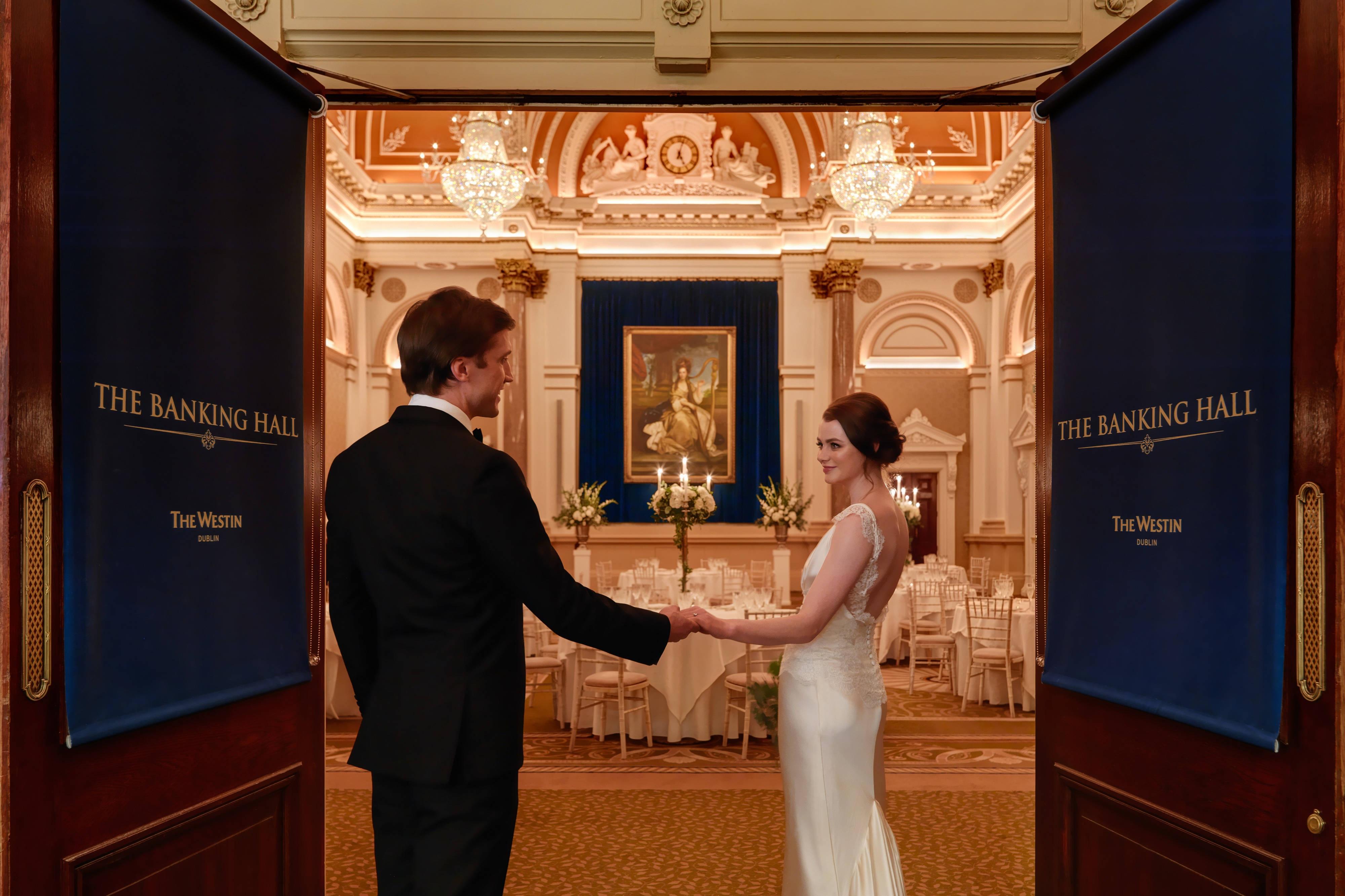 Couple franchissant les portes principales de la salle Banking Hall