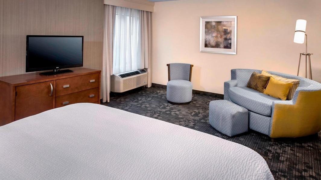 Sitzbereich eines Gästezimmers mit Kingsize-Bett