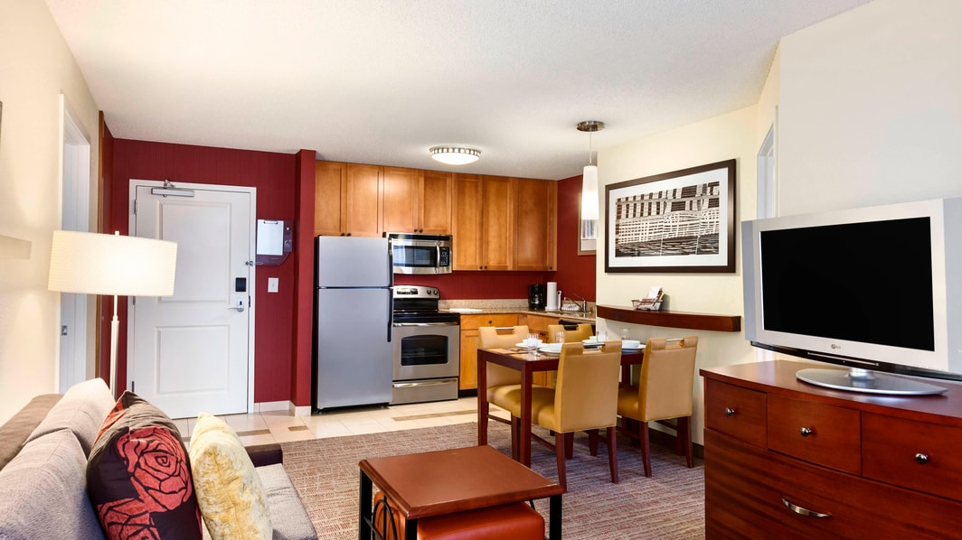 Two bedrooms, sofa, TV, dining area, refrigerator, stove, microwave