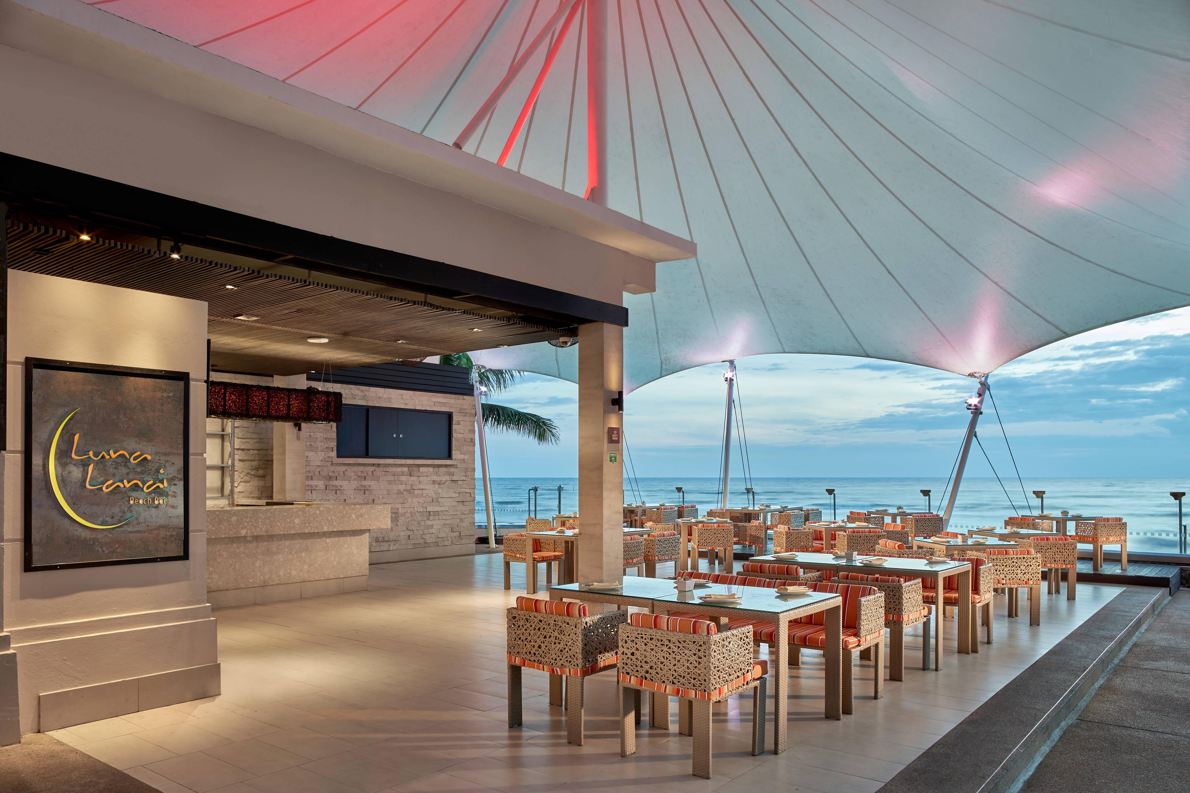 Espace repas en plein air du restaurant Luna Lanai au bord de l'eau