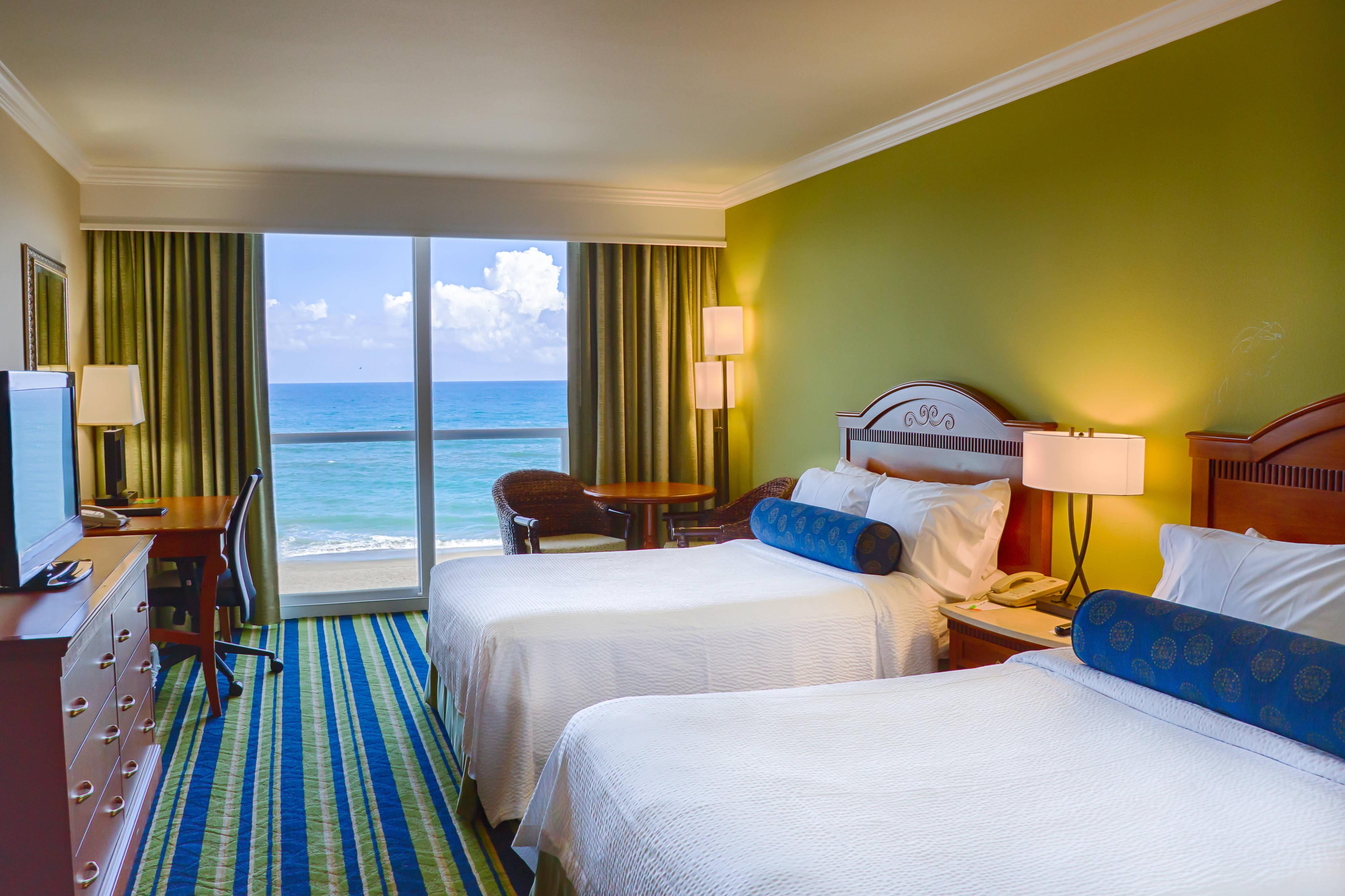 Chambre avec deux lits doubles et vue sur l'océan