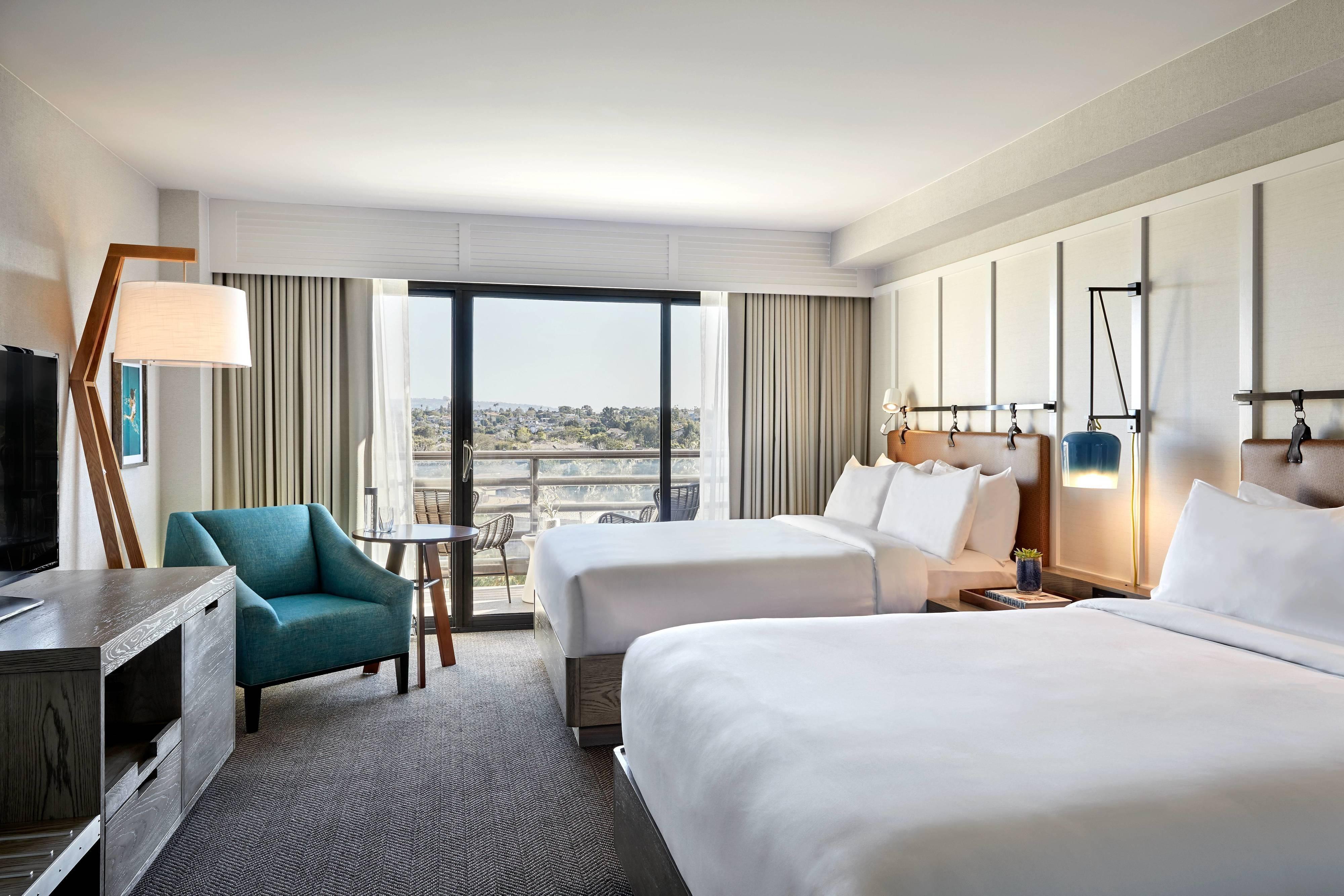 Gästezimmer mit zwei Queensize-Betten und Blick auf den Golfplatz