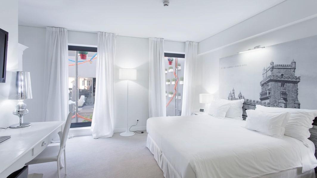 Gästezimmer mit Balkon und weißer Einrichtung – Blick von der offenen Terrasse