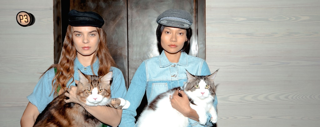 Two women holding cats