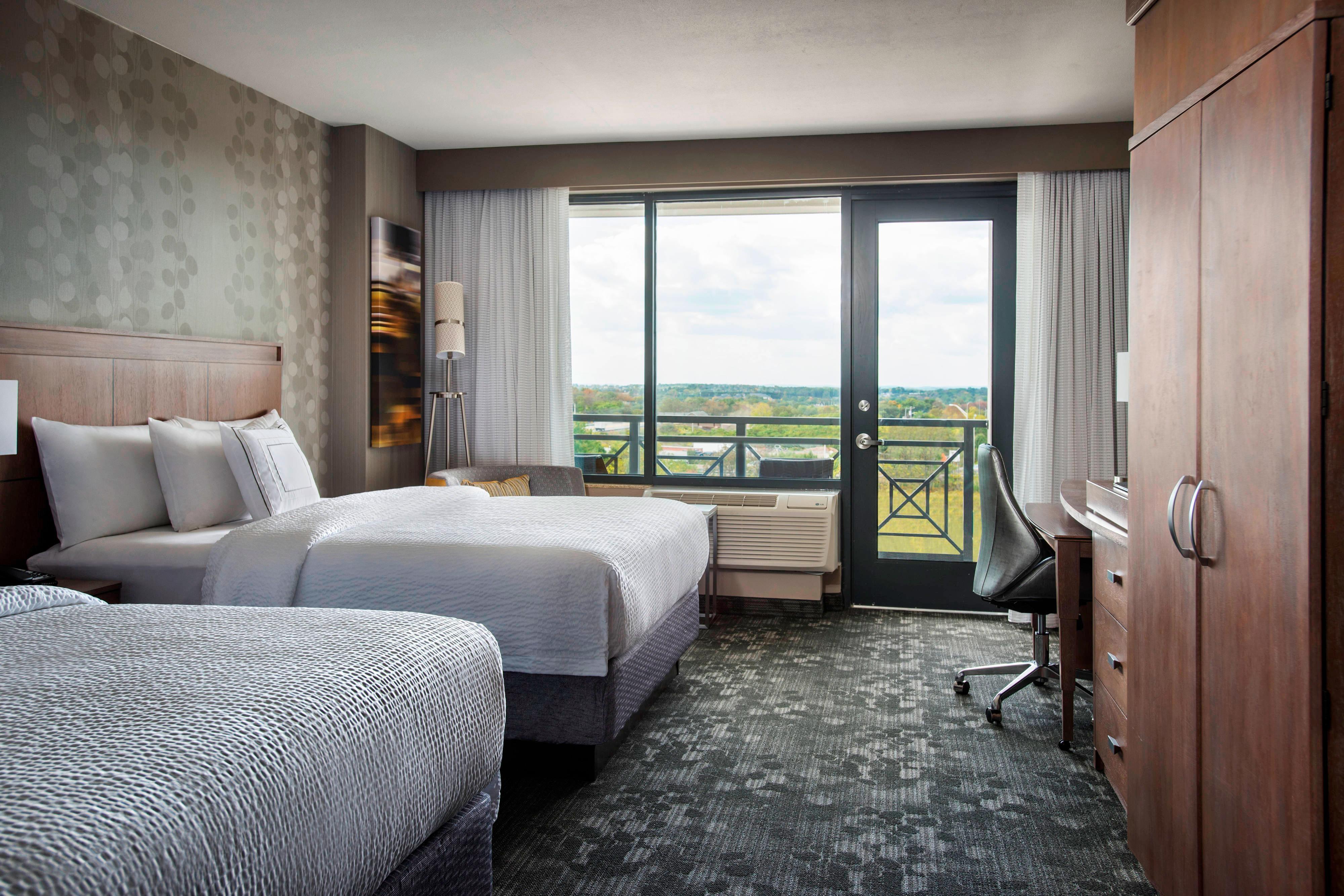 Gästezimmers mit zwei Queensize-Betten und Balkon