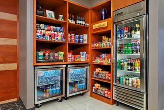 glass-doored refrigerator and shelving units stocked with food and drinks