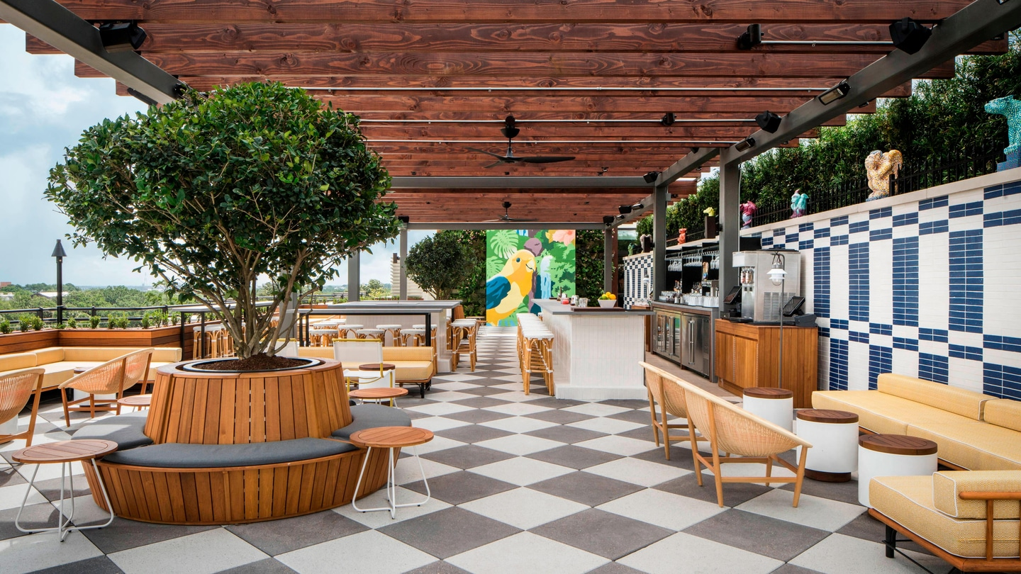 Green walls complement a colorful mural atop the rooftop bar