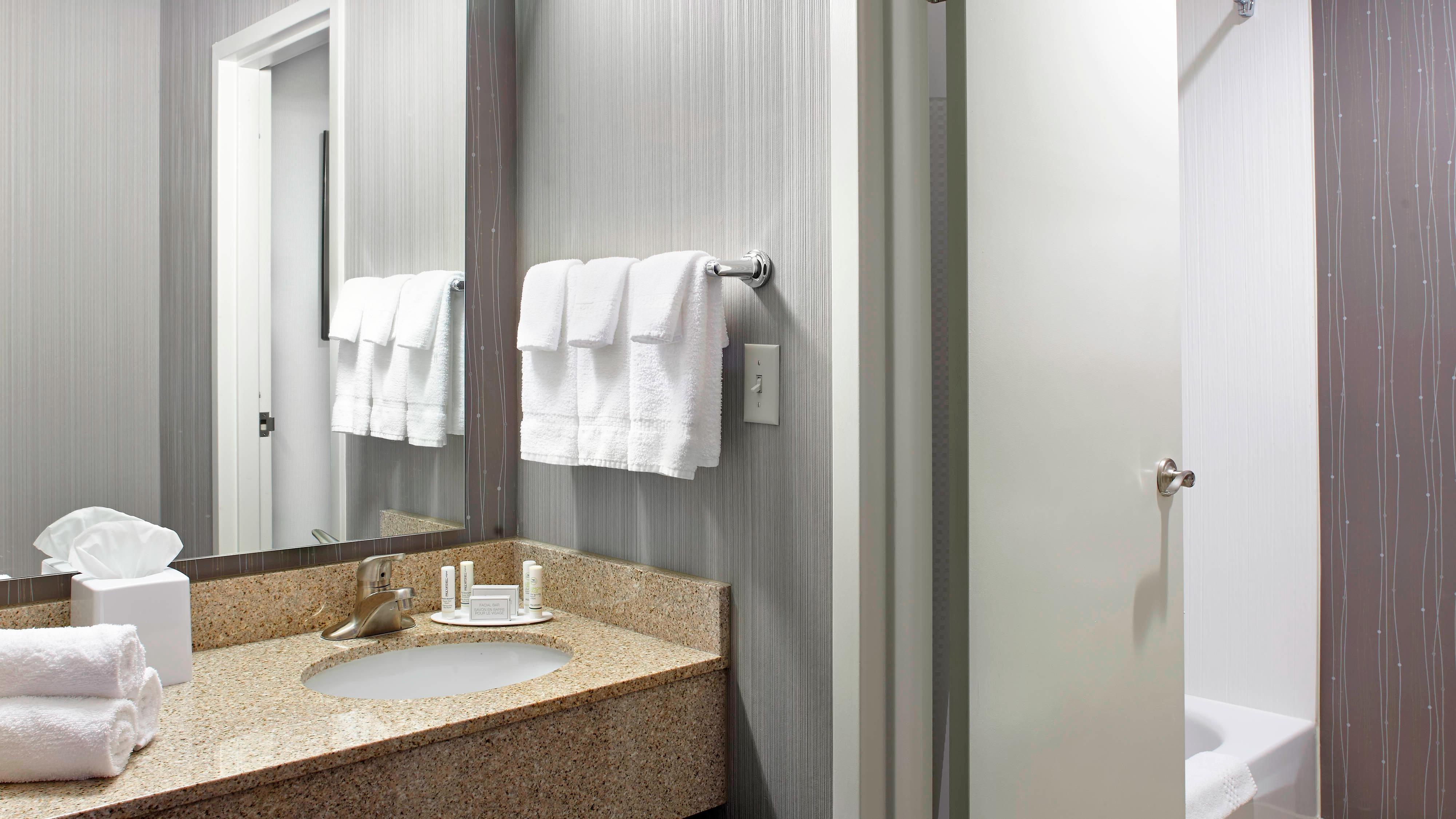 Baño de la habitación con tocador y combinación de bañera y ducha