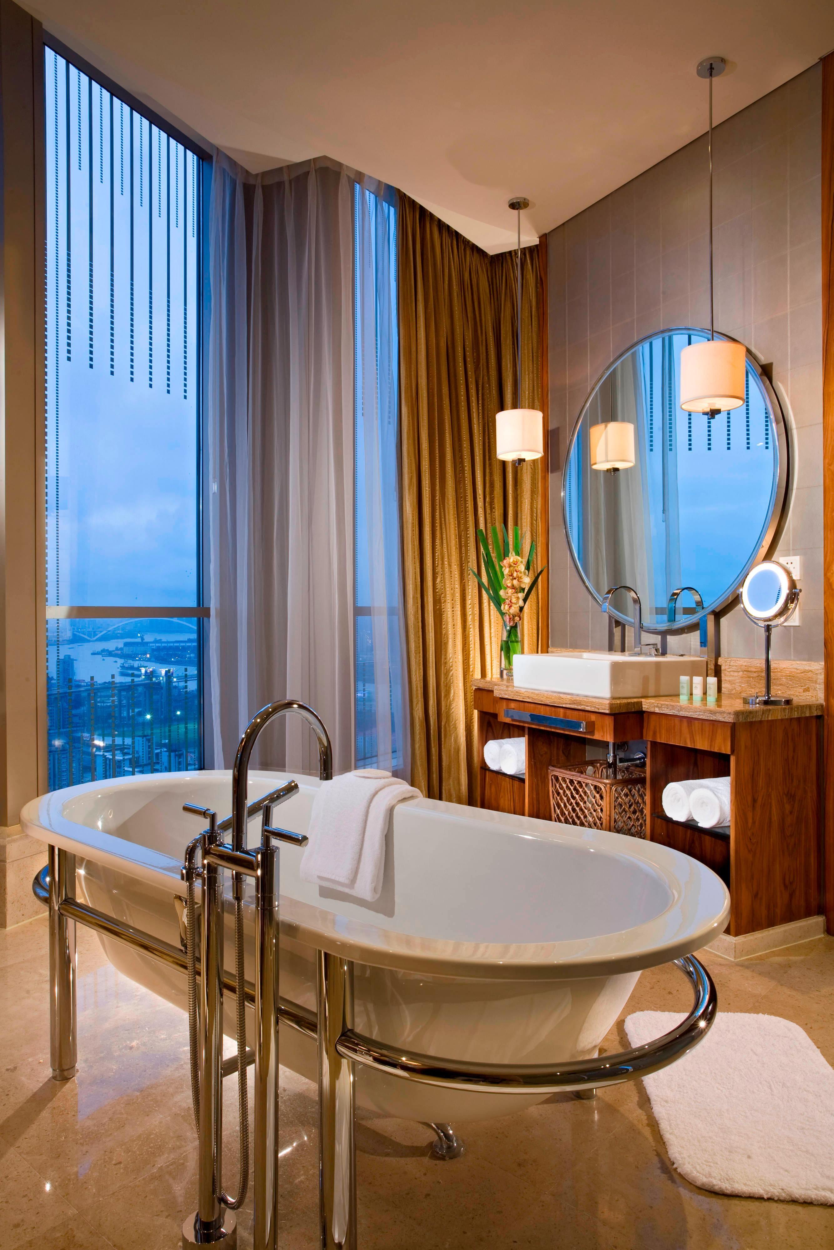 Salle de bain de la suite Executive avec vue de nuit sur le Bund Center