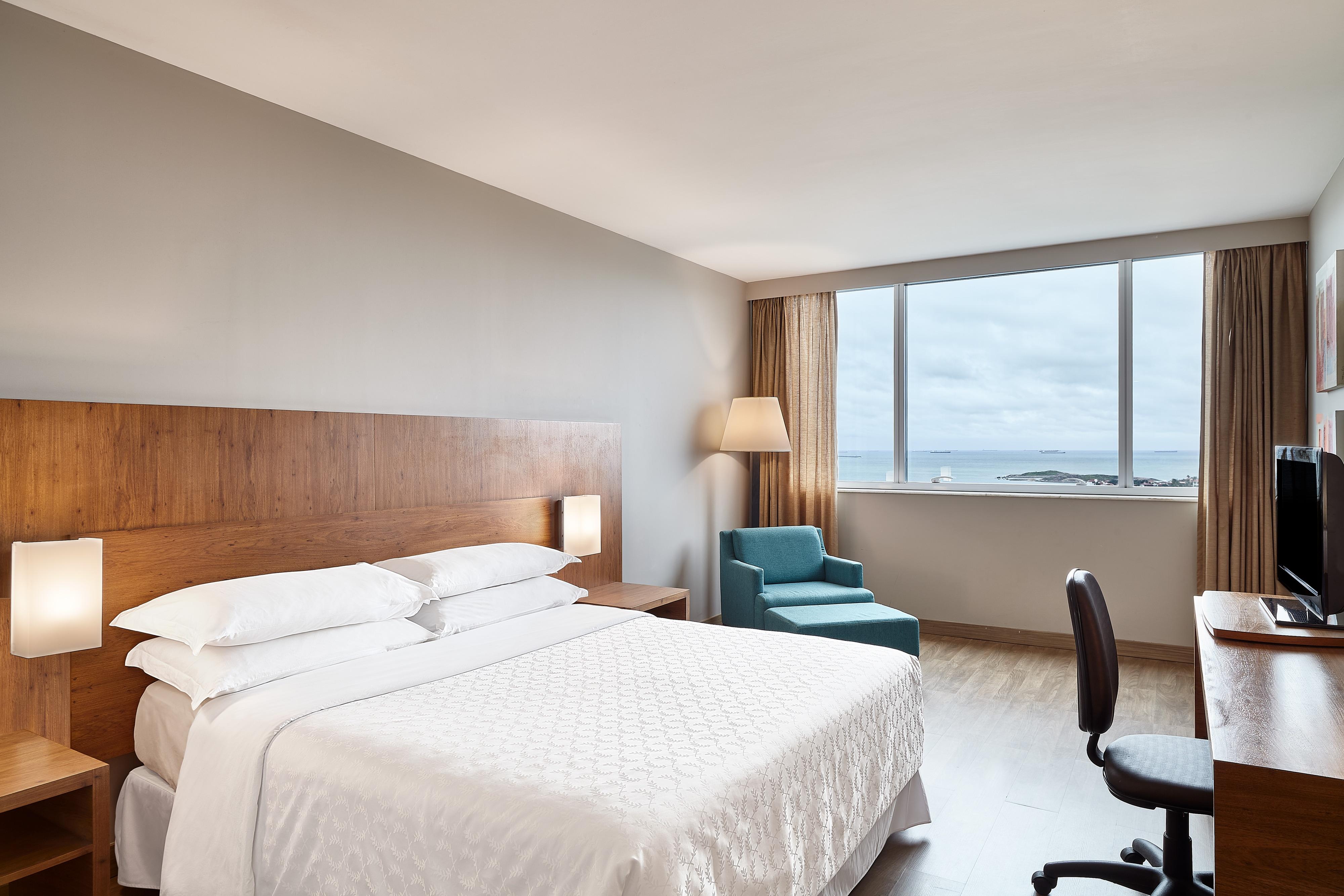 Chambre avec lit queen size et vue sur l'océan