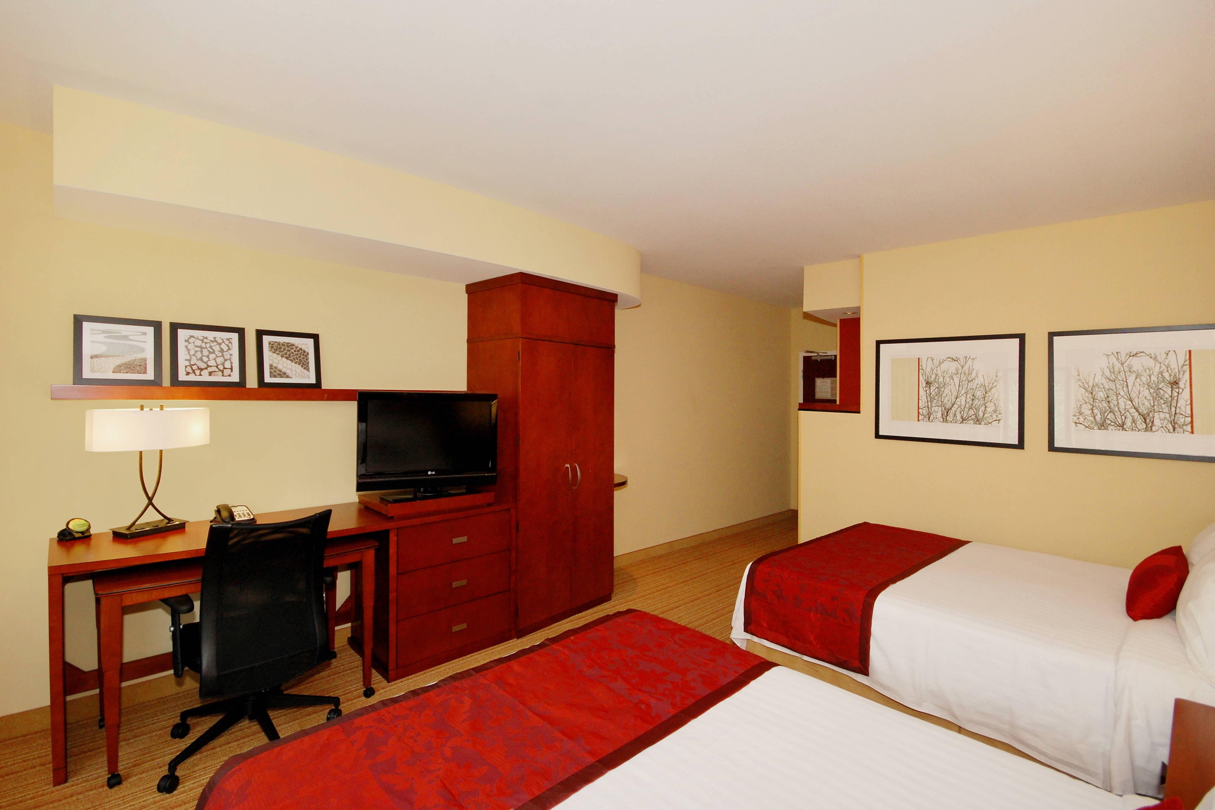 Espace de travail d'une chambre avec deux grands lits