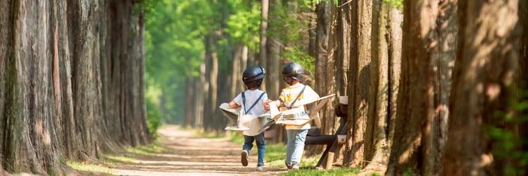 새싹이 돋은 숲을 뛰어 다니는 두 명의 아이