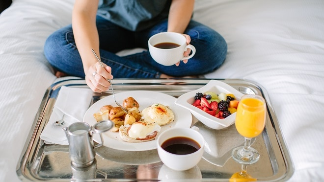 Person sitting on bed with breakfast tray