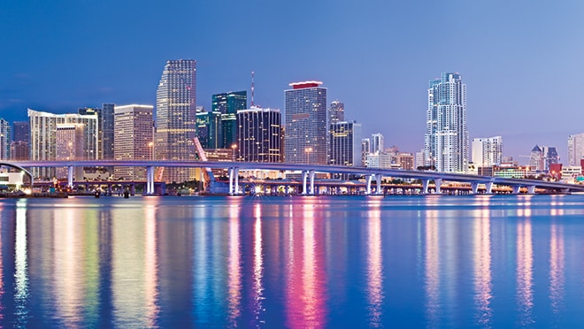 View of Miami skyline at night reflecting off body of water