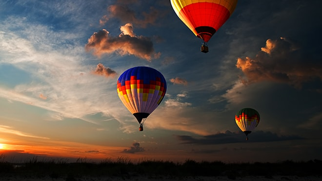 Three hot air balloons in the sky at sunset