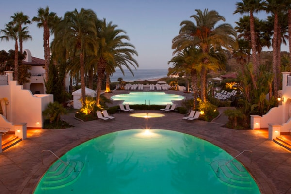 Pools and palm trees with beach in the background