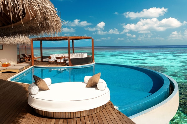 A wood hut with a pool overlooking the ocean